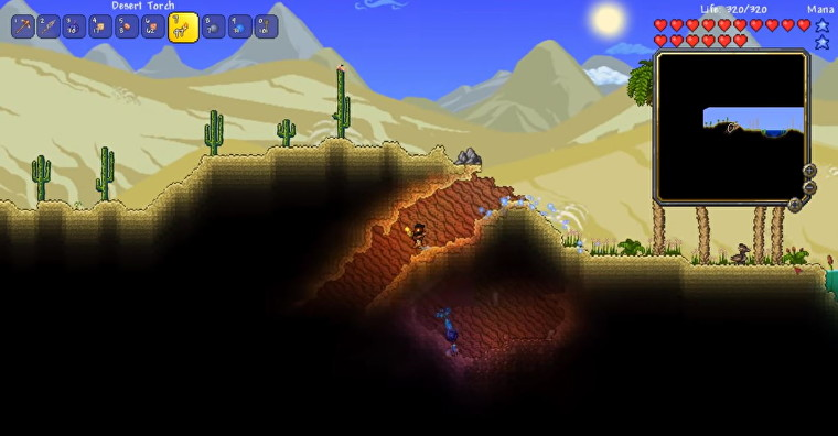 Una imagen de Terraria que muestra al personaje del jugador en un bioma del desierto.  Están sosteniendo una antorcha mientras descienden a un túnel oscuro e inexplorado.
