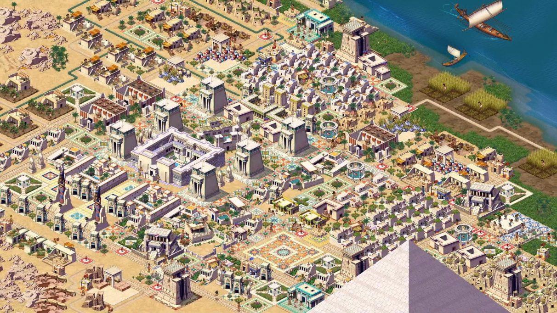 Una segunda captura de pantalla promocional de una ciudad en Pharaoh: A New Era.  Esta ciudad es más grandiosa.  Las orillas del Nilo son visibles en la esquina superior derecha, y la punta de una pirámide asoma desde la parte inferior de la captura de pantalla.