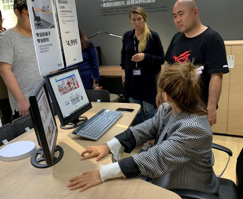 Una foto de uno de los talleres de diseño de Asus e Ikea, que muestra a un representante de Asus de pie junto a una mujer sentada en un escritorio Ikea existente.
