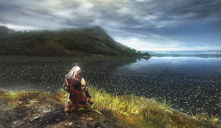 Geralt de The Witcher se arrodilla en una orilla cubierta de hierba con vistas a un enorme lago, con una montaña en la distancia.  Es bonito, para 2007.