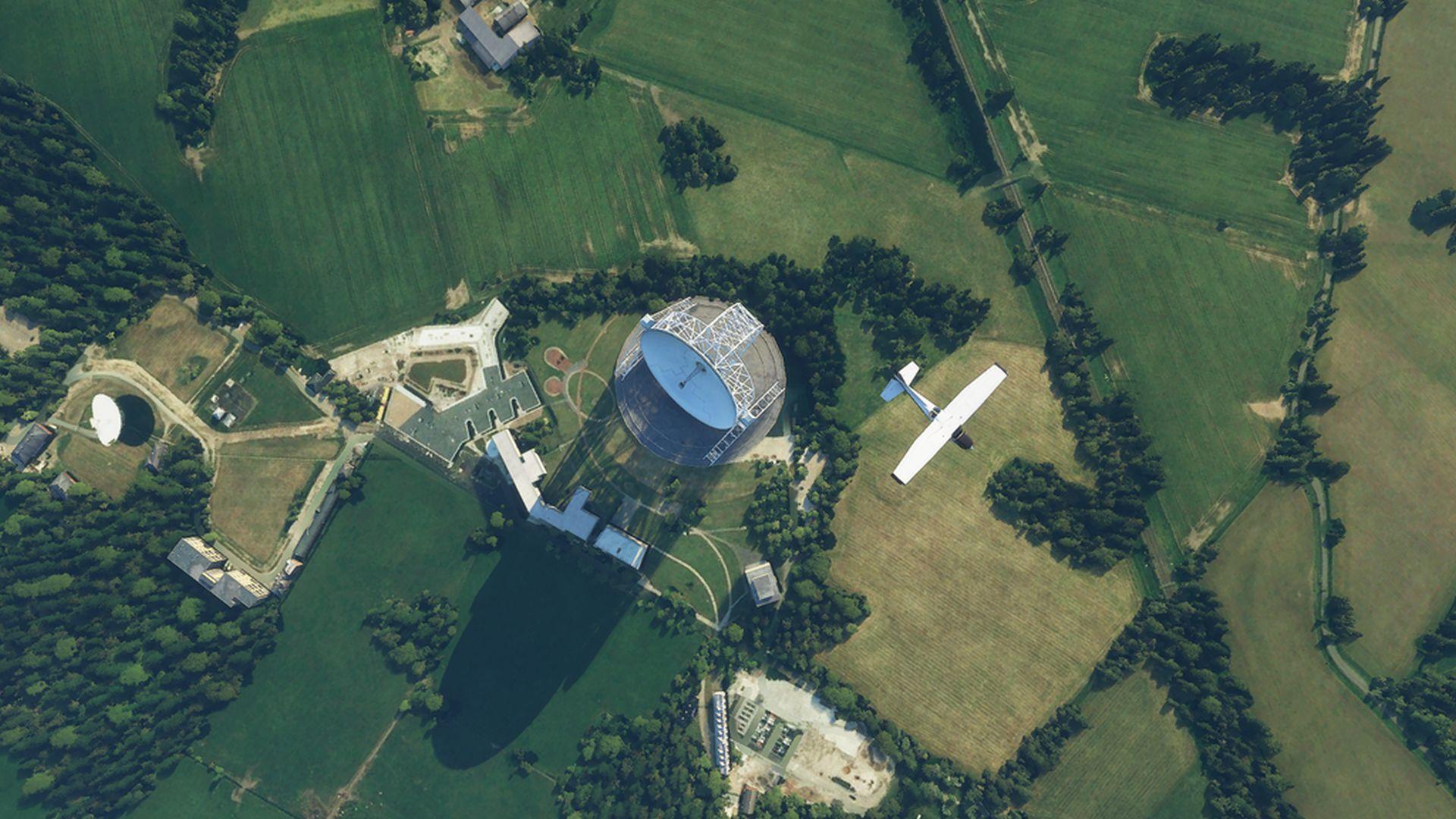 Una captura de pantalla de Microsoft Flight Simulator de arriba hacia abajo.  Un avión sobrevuela un radiotelescopio, se instala en la campiña inglesa
