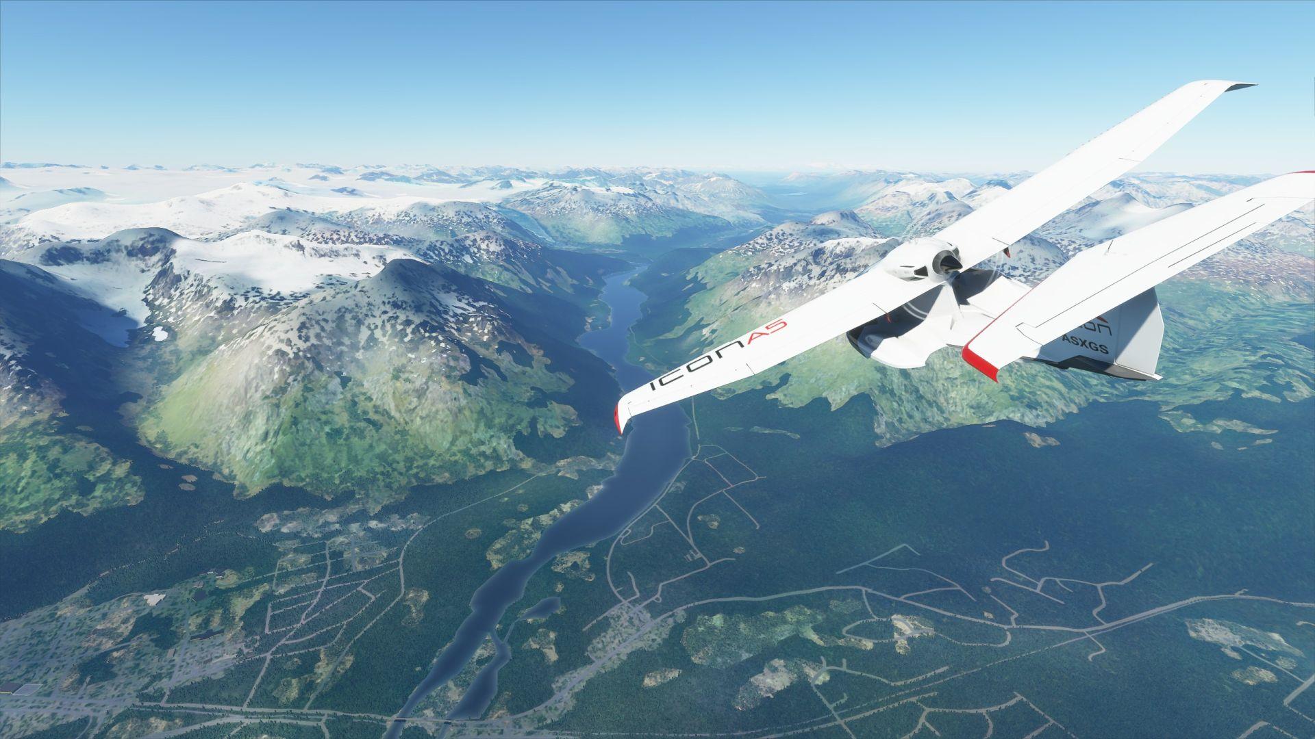 Una captura de pantalla de Microsoft Flight Simulator.  Una avioneta sobrevuela el paisaje de Alaska.  Un río llano corre entre dos montañas.