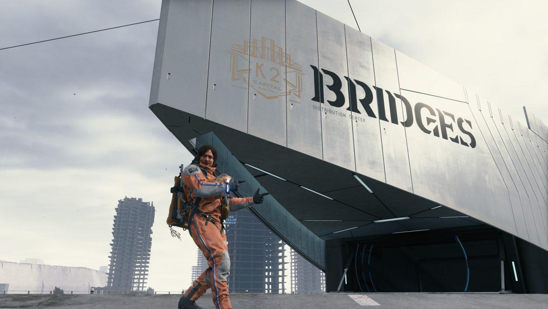 Una captura de pantalla de Sam Bridges haciendo un cartel con el pulgar hacia arriba fuera de las instalaciones de un depósito de Bridges en Death Stranding.