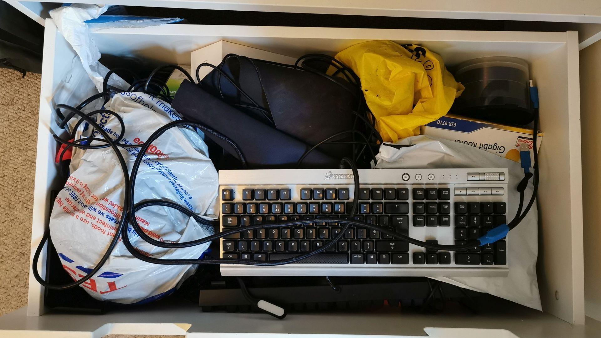 Una fotografía de un dibujo lleno de piezas de PC: un teclado, una pila de CD, varios cables, bolsas de plástico con gubbins desconocidos.