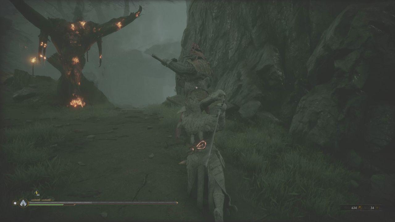 Una captura de pantalla de Mortal Shell que muestra al personaje del jugador usando la habilidad Endurecimiento.  Se han congelado como una estatua de piedra, con su espada medio levantada para atacar, mientras un gran enemigo está a punto de lanzar un fuerte ataque sobre ellos.