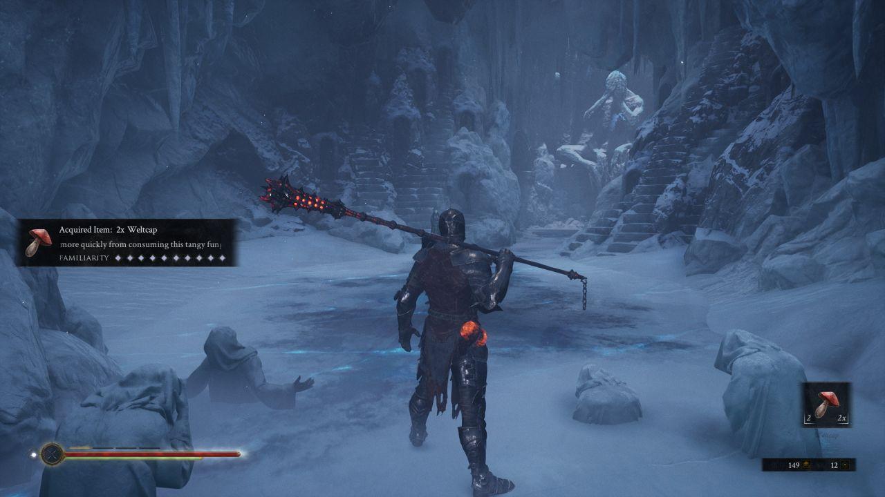 Una captura de pantalla de Mortal Shell que muestra al personaje del jugador, todavía con armadura de placas pero empuñando una gran maza sobre un hombro, mirando hacia una cueva.  El suelo es de hielo, y las estatuas de figuras encapuchadas y angustiadas están medio encajonadas junto al jugador.  En el otro extremo de la habitación hay una gran estatua humanoide en posición sentada.
