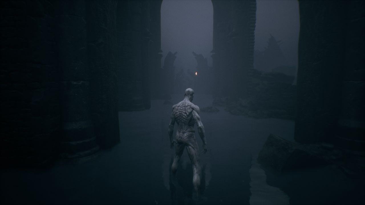 Una captura de pantalla del personaje del jugador en Mortal Shell, en vista en tercera persona.  Parecen desnudos y su piel es gris.  Son musculosos, pero de una forma desconcertante.  Están sumergidos hasta los tobillos en el agua, en una especie de catacumba subterránea con arcos de piedra altos y rotos.
