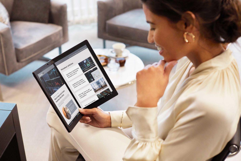 Una mujer disfruta del vino de negocios en una foto de 'estilo de vida' del Lenovo ThinkPad X1 Fold.
